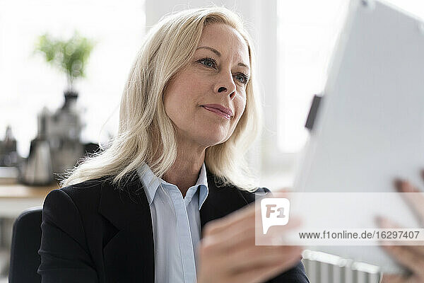 Close-up of confident female entrepreneur using digital tablet in home office