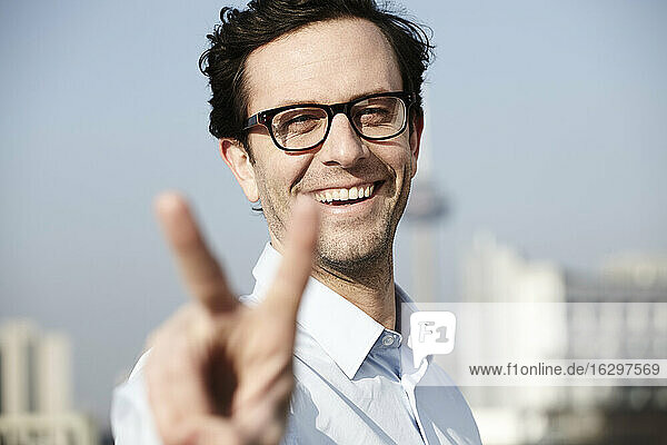 Portrait of smiling man showing victory sign