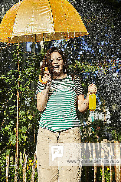 Young laughing woman with umbrella and limonade in garden