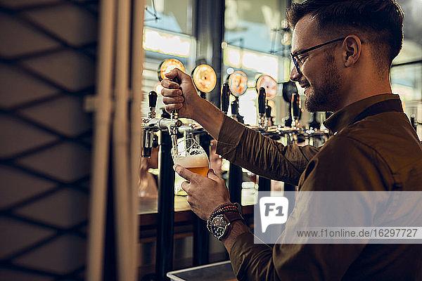 Lächelnder Barkeeper zapft Bier in einer Kneipe Lächelnder Barkeeper zapft Bier in einer Kneipe