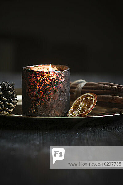 Christmas decoration with tea light candle  cinnamon sticks  slices of dried oranges and cone on plate  studio shot