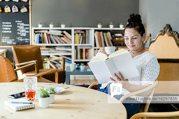 Young woman holding coffee cup reading book while sitting at table in cafe