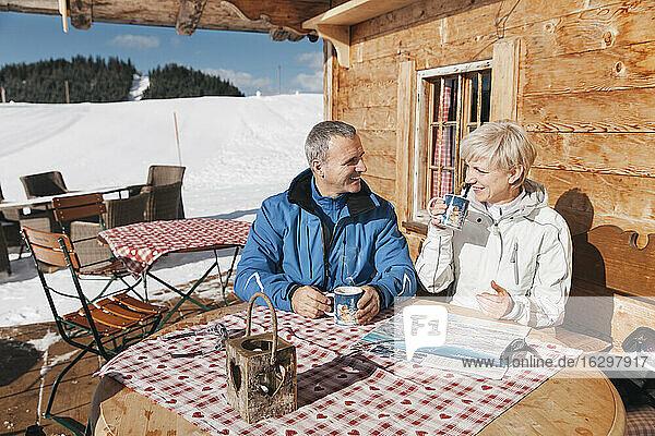 Germany  Bavaria  Winklmoosalm  Mature couple on terrace of alpine hut