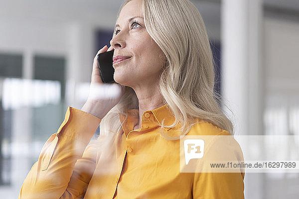 Nahaufnahme einer Geschäftsfrau  die über ein Smartphone im Büro zu Hause spricht  gesehen durch ein Fenster