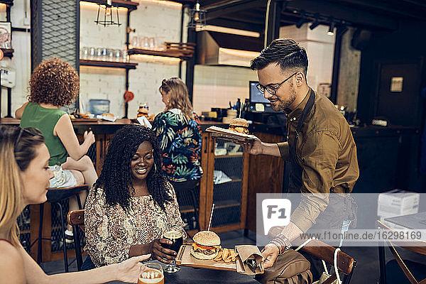 Kellner serviert Hamburger für Frau in einer Kneipe Kellner serviert Hamburger für Frau in einer Kneipe