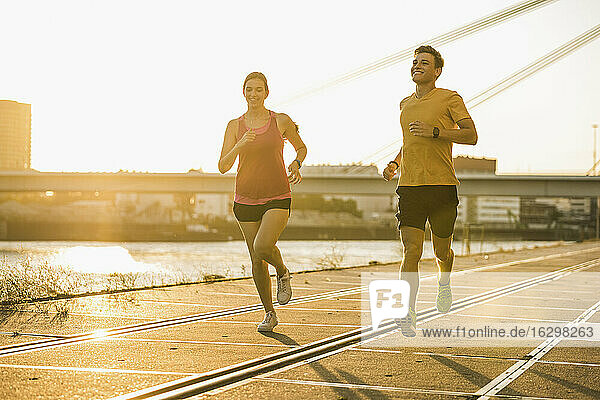 Smiling male and female jogging at harbor during sunny day