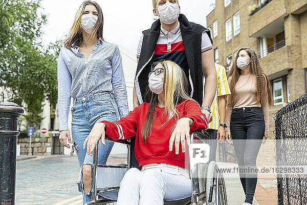 Männer und Frauen mit einer behinderten Freundin tragen in der Stadt Masken
