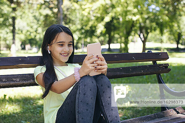 Smiling girl using phone while sitting on bench in park