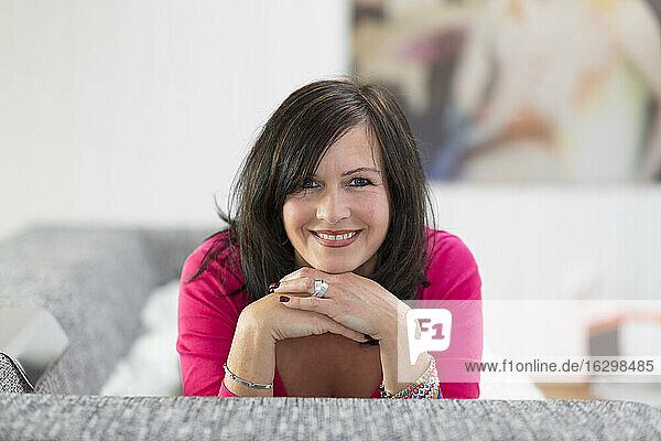 Porträt einer lächelnden Frau auf dem Sofa liegend