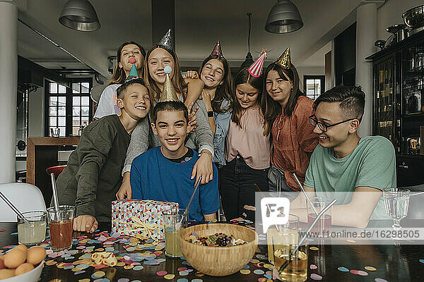 Happy friends standing by birthday boy at dining table