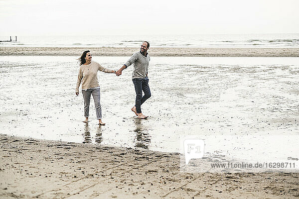 Couple holding hands while walking at beach against sky