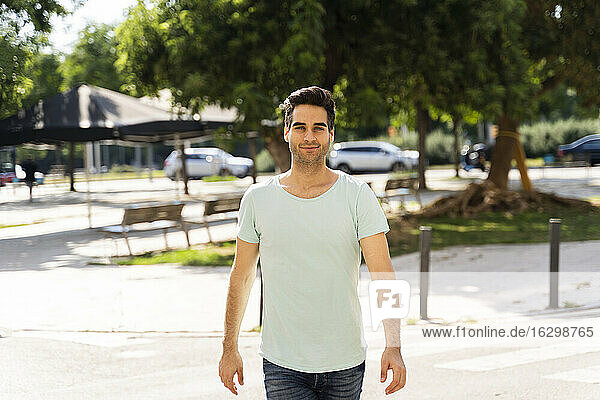 Confident man walking in city during sunny day