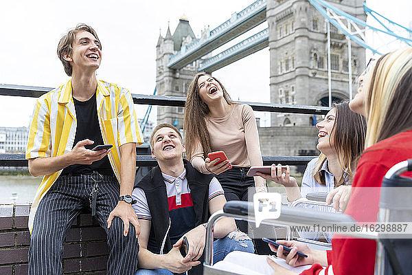 Fröhliche männliche und weibliche Freunde mit Mobiltelefonen an der Tower Bridge  London  UK