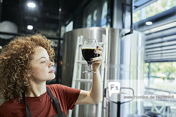 Woman working in craft brewery checking quality of a beer