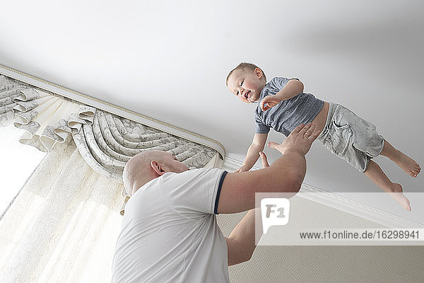 Father throwing son in the air at home