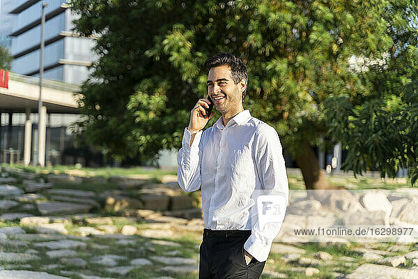 Smiling male professional talking over smart phone while standing in park