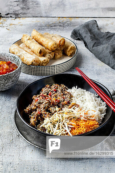 Bowl of fried sesame beef  salad and rice with dipping sauce and spring rolls in background