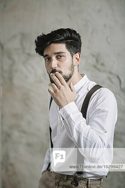 Man smoking while standing against wall
