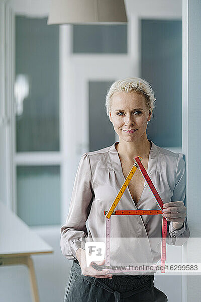 Confident female architect holding model while standing in office