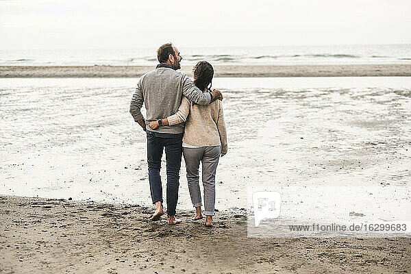 Couple looking at sea while standing on beach during sunset