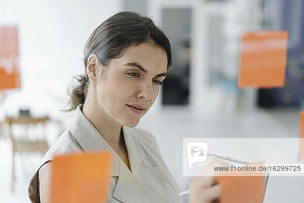 Young woman writing on sticky note while standing at office