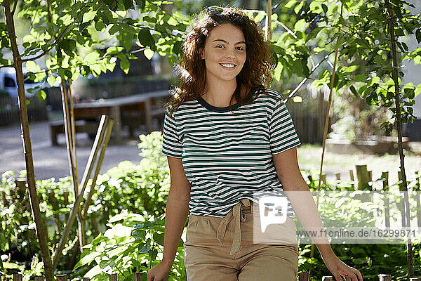Young smiling woman looking at camera in garden