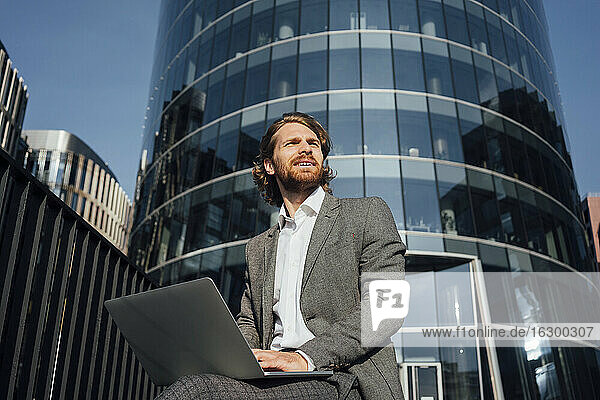 Thoughtful young male entrepreneur sitting with laptop while looking away in financial district