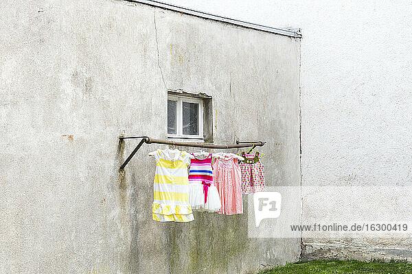 Deutschland  düsterer Hinterhof mit Kinderkleidern  die an der Kleiderstange hängen