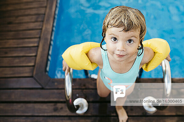 Little girl with armbands at ladder of swimming pool