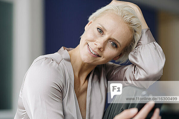 Close-up of smiling businesswoman using smart phone while sitting in office