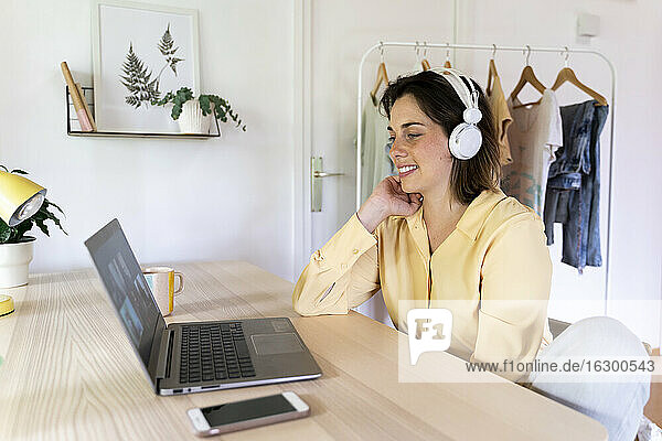 Happy young woman enjoying video call with friends through laptop at home