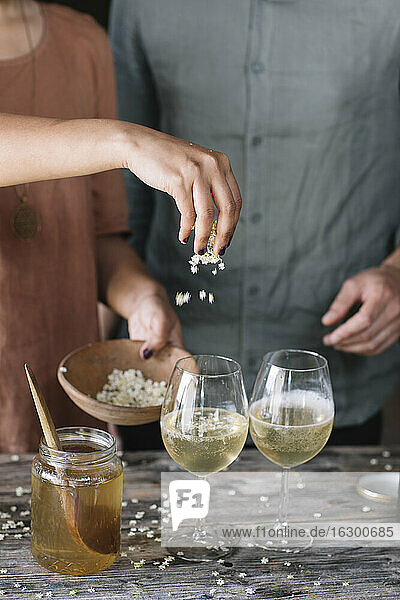 Midsection of woman sprinkling flowers on cocktail in wineglass while standing by boyfriend