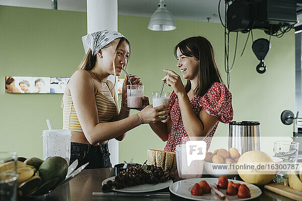 Teenage girls standing in kitchen drinking fresh fruit smoothies with drinking straws
