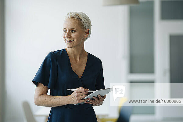 Smiling female entrepreneur holding digital tablet contemplating while standing in office