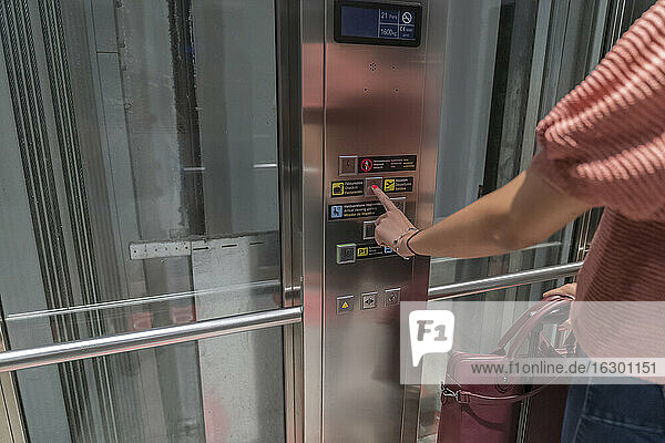 Close-up of young woman pressing elevator button
