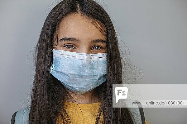 Girl with protective face mask standing against gray wall