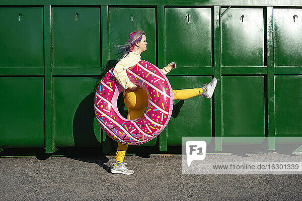 Young woman with dyed hair and floating tyre walking in front of green container
