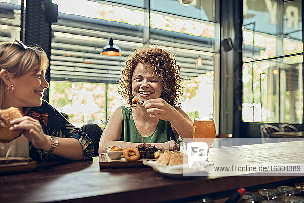 Two happy female friends having a snack at the counter in a pub
