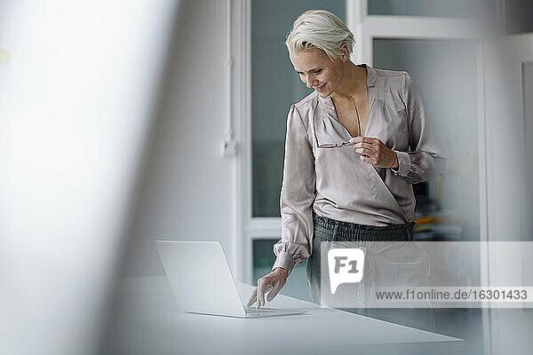 Smiling female entrepreneur using laptop on desk while standing in office