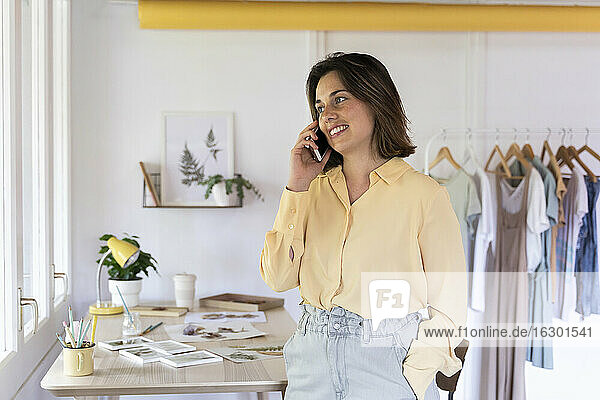 Happy clothing store owner talking on smart phone while looking away