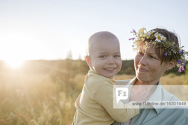 Happy woman wearing wreath while carrying son during sunny day
