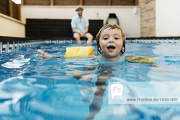 Little girl in swimming pool  her uncle on poolside