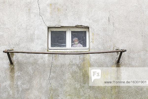 Deutschland  Puppe sitzt hinter dem Fenster einer Garage