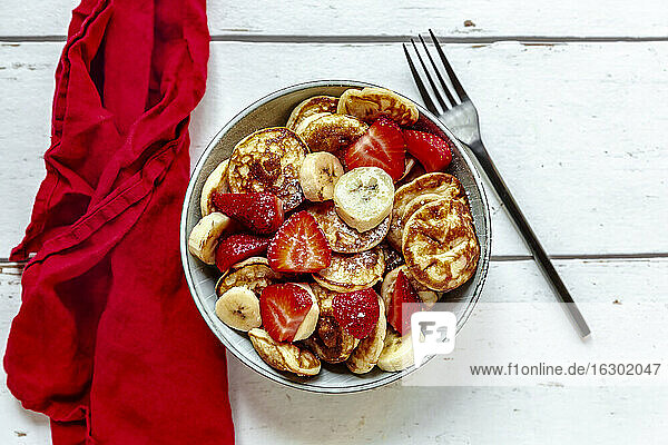 Bowl of mini pancakes with strawberries and bananas