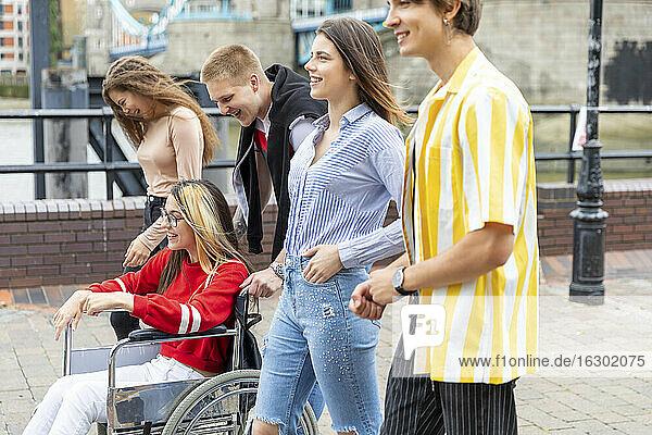 Glückliche Männer und Frauen mit behinderter Freundin verbringen ihre Freizeit in der Stadt