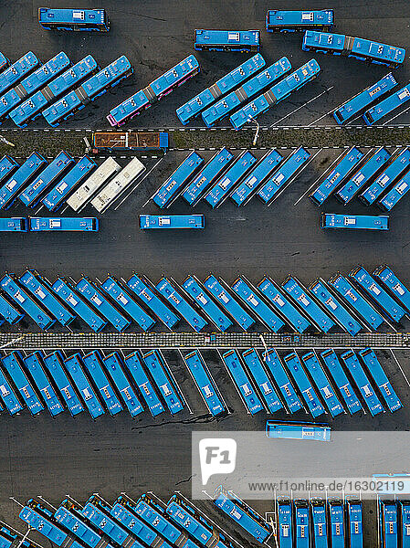 Aerial view of parking lot filled with blue buses