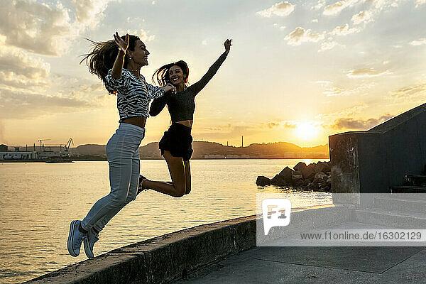 Young women enjoying while jumping at promenade during sunset