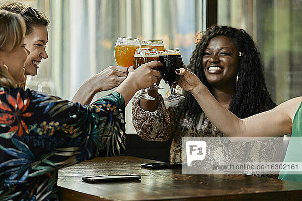 Happy female friends clinking craft beer glasses in a pub