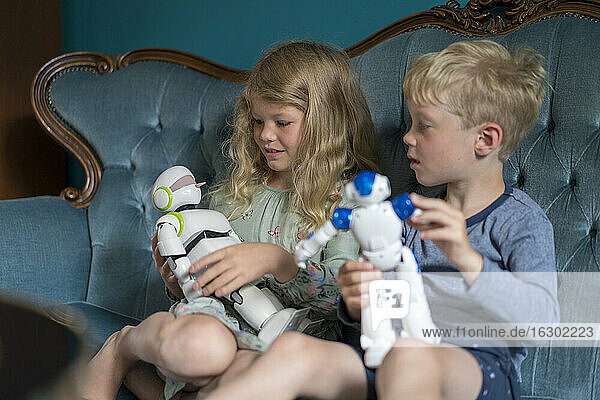 Siblings playing with robots while sitting on sofa at home