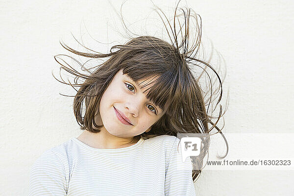 Portrait of smiling little girl with wafting hair